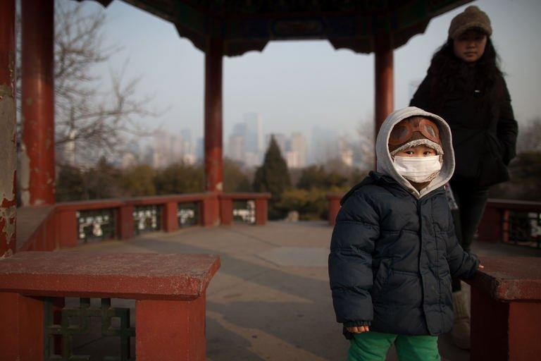 A child wearing a facemask walks through Beijing on January 15, 2013. Shares in a Chinese facemask manufacturer have soared as investors looked for opportunities to profit from the severe air pollution that has blanketed large swathes of China