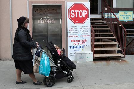 FILE PHOTO: A sign warning people of measles in the ultra-Orthodox Jewish community of Williamsburg, two days after New York City Mayor Bill de Blasio declared a public health emergency in parts of Brooklyn in response to a measles outbreak, is seen in New York, U.S., April 11, 2019. REUTERS/Shannon Stapleton/File Photo