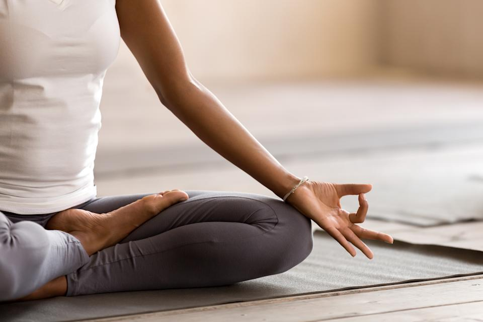 Yogi black woman practicing yoga lesson, breathing, meditating, doing Ardha Padmasana exercise, Half Lotus pose with mudra gesture, working out, indoor close up. Well being, wellness concept