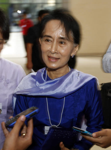 Myanmar opposition leader Aung San Suu Kyi speaks to journalists as she leaves Myanmar International Convention Center after attending the first day of the three-day World Economic Forum for East Asia in Naypyitaw, Myanmar, Wednesday, June 5, 2013. (AP Photo/Khin Maung Win)