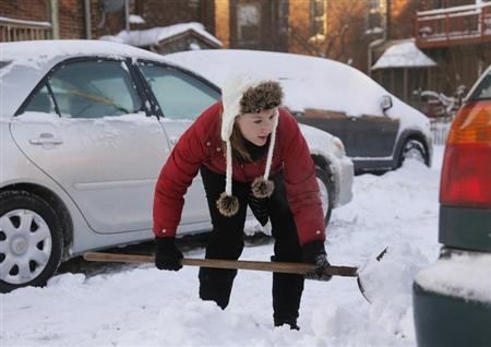 Jessica Corner shovels snow so she can move her vehicle from behind the apartment building she lives in during bitter cold temperatures in Detroit,