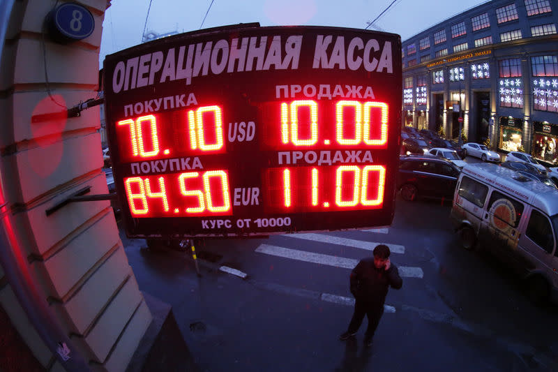 A man stands next to a building under a board showing currency exchange rates in Moscow