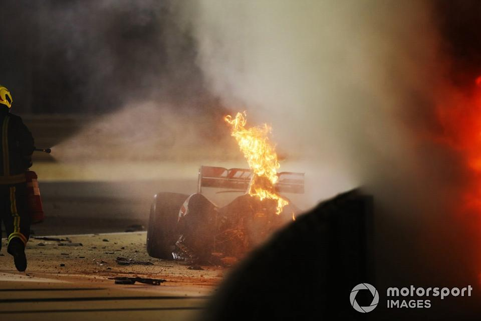 """A fire marshal extinguishes the flames on the car of Romain Grosjean, Haas VF-20<span class=""""copyright"""">Andy Hone / Motorsport Images</span>"""