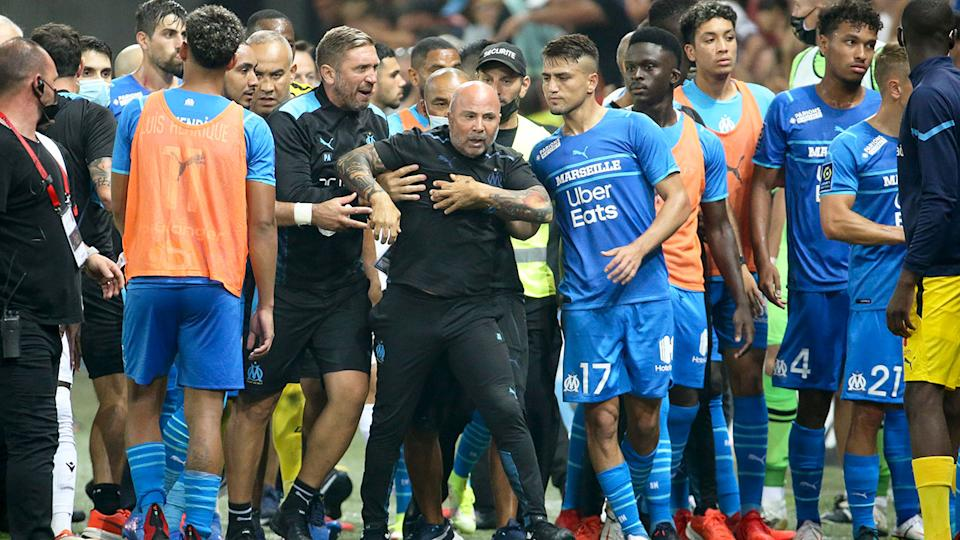 Seen here, Marseille coach Jorge Sampaoli is restrained by officials after reacting angrily to the incident.