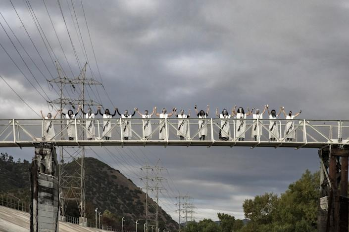 Women in white caftans emblazoned with an image of a rifle stand triumphantly on a pedestrian bridge over the L.A. River