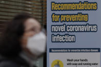 A woman wearing a face mask walks by a banner showing precautions against the coronavirus in downtown Seoul, South Korea, Thursday, Nov. 26, 2020. (AP Photo/Lee Jin-man)