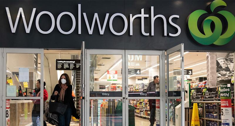 Photo shows woman wearing mask walking out of Woolworths store.