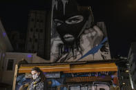 A woman wearing a face mask to curb the coronavirus walks in front of a mural created by street artist INO in the Psiri district of Athens, on Friday, Oct. 23, 2020. (AP Photo/Petros Giannakouris)