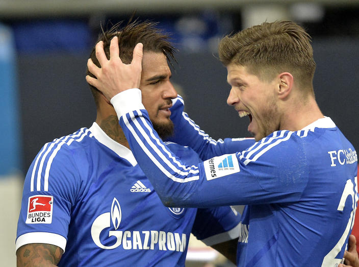 Schalke's Klaas-Jan Huntelaar of the Netherlands, right, celebrates Schalke's Kevin-Prince Boateng of Ghana after the opening goal during the German Bundesliga soccer match between FC Schalke 04 and VfL Wolfsburg in Gelsenkirchen, Germany, Saturday, Feb. 1, 2014. (AP Photo/Martin Meissner)
