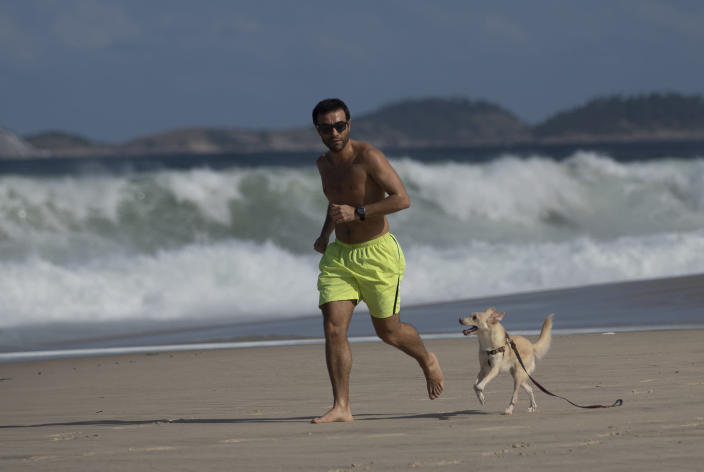 A man runs with his dog on Copacabana Beach. (AP)