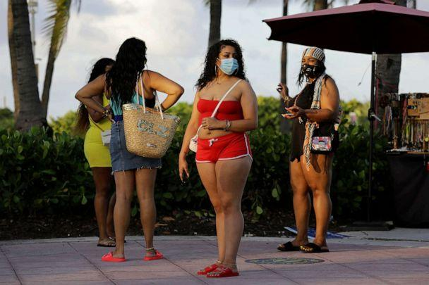 PHOTO: Women wearing protective face masks walk along Ocean Drive amid the coronavirus pandemic, July 24, 2020, in Miami Beach, Fla. (Lynne Sladky/AP)