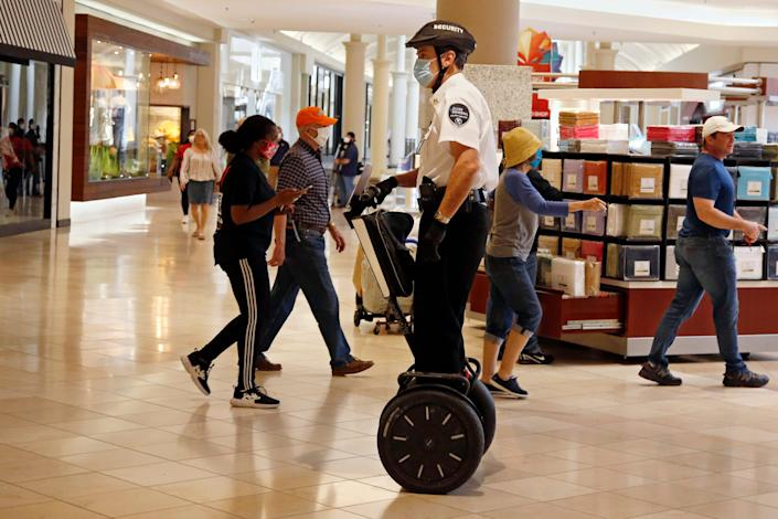 A security guard wearing a mask and riding a Segway patrols inside Penn Square Mall as the mall reopens in Oklahoma City in this May 1, 2020 file photo.