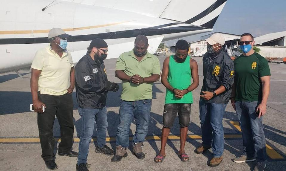 "Federal agents with the Federal Bureau of Investigations and Drug Enforcement Administration arrived in Haiti Friday, March 5, 2021 to fly out two individuals. Lissner Mathieu, 55, in the light green shirt, is a U.S. fugitive known as ""Ti-Nwa."" Next to him, in a a dark green shirt, is Peterson ""Ti Peter Vilaj"" Benjamin (right), a Haitian national. Both men were arrested earlier in the week by Haiti National Police."