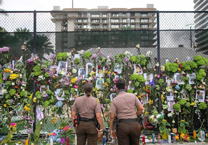 Miami-Dade police officers look at photos of missing residents on a fence in front of Champlain Towers South condo in Surfside, Fla. Tuesday, June 29, 2021.
