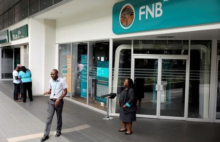 First National Bank (FNB) staff members stand outside their bank to notify customers that the bank is closed due to load shedding, at the mall of the south in Johannesburg