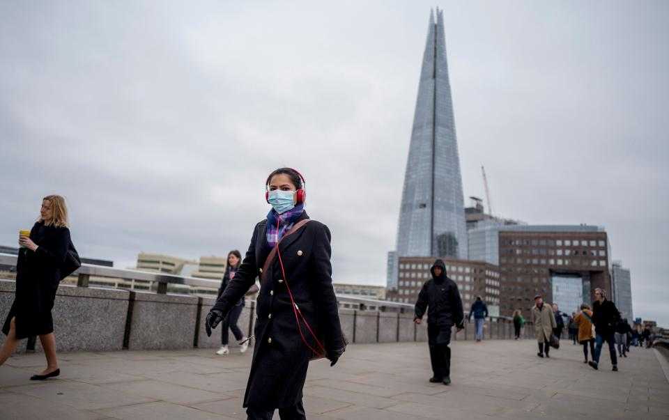 A commuter wears a mask whilst walking across a quiet London Bridge into the City of London during the morning rush hour on March 18, 2020 as people take precautions amid the coronavirus outbreak. - The British government will on Wednesday unveil a raft of emergency powers to deal with the coronavirus epidemic, including proposals allowing police to detain potentially infected people to be tested. (Photo by Tolga AKMEN / AFP) (Photo by TOLGA AKMEN/AFP via Getty Images)