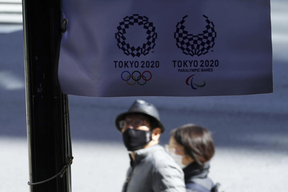 People wearing protective masks to help curb the spread of the coronavirus walk near a banner of Tokyo 2020 Olympic and Paralympic Games Wednesday, March 3, 2021, in Tokyo. The Japanese capital confirmed more than 310 new coronavirus cases on Wednesday. (AP Photo/Eugene Hoshiko)