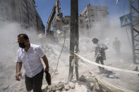 Pedestrians pass through clouds of dust as heavy construction equipment is used to sift through rubble to uncover valuables before it is transported away from the scene of a building destroyed in an airstrike prior to a cease-fire that halted an 11-day war between Gaza's Hamas rulers and Israel, Thursday, May 27, 2021, in Gaza City. (AP Photo/John Minchillo)