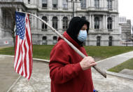"""A man representing a group called """"The American People"""" walks with a flag during a protest rally for President Donald Trump ahead of the inauguration of President-elect Joe Biden and Vice President-elect Kamala Harris at the New York State Capitol Sunday, Jan. 17, 2021, in Albany, N.Y. (AP Photo/Hans Pennink)"""