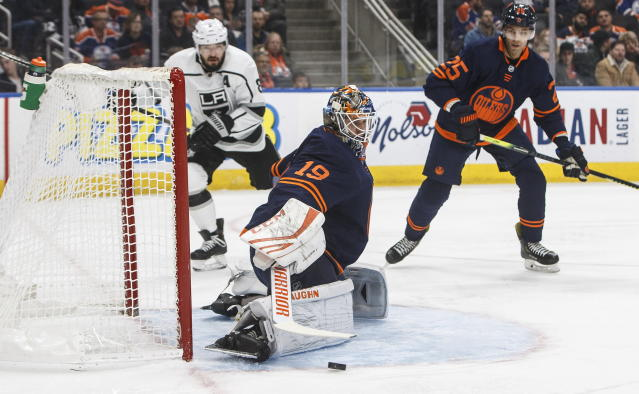 Los Angles Kings' Drew Doughty (8) watches as Edmonton Oilers goalie Mikko Koskinen (19) makes a save and Darnell Nurse (25) defends during the first period of an NHL hockey game Friday, Dec. 6, 2019, in Edmonton, Alberta. (Jason Franson/The Canadian Press via AP)