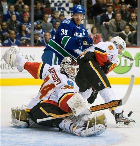 Calgary Flames goalie Miikka Kiprusoff, bottom, of Finland, makes a toe save as Mark Giordano, right, defends against Vancouver Canucks' Henrik Sedin, of Sweden, during the first period of an NHL hockey game game in Vancouver, British Columbia, on Wednesday, Jan. 23, 2013. (AP Photo/The Canadian Press, Darryl Dyck)