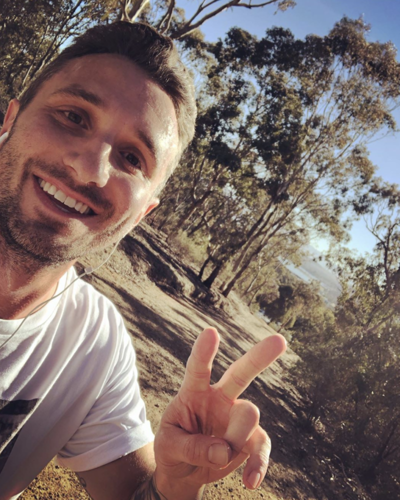 Tommy Little wears a white t-shirt and shows a peace sign in a post-run selfie in the bush