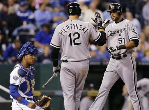 Chicago White Sox's A.J. Pierzynski (12) celebrates with Alex Rios (51) after Rios hit a solo home run during the seventh inning of a baseball game against the Kansas City Royals, Tuesday, Sept. 18, 2012, in Kansas City, Mo. (AP Photo/Charlie Riedel)