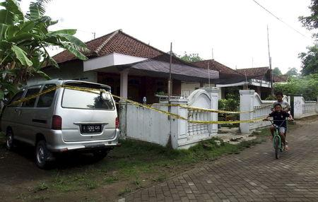 Children ride a bike past a house with police tape around it, following a raid by anti-terror police in Mojokerto