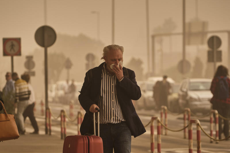 A passenger covers his nose and mouth in a cloud of red dust at the airport in Santa Cruz de Tenerife, Spain, Sunday, Feb. 23, 2020. Flights leaving Tenerife have been affected after storms of red sand from Africa's Saharan desert hit the Canary Islands. (AP Photo/Andres Gutierrez)