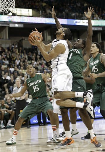 Wake Forest's C.J. Harris, center, drives past Miami's Durand Scott, right, and Rion Brown, left, during the first half of an NCAA college basketball game in Winston-Salem, N.C., Saturday, Feb. 23, 2013. (AP Photo/Chuck Burton)
