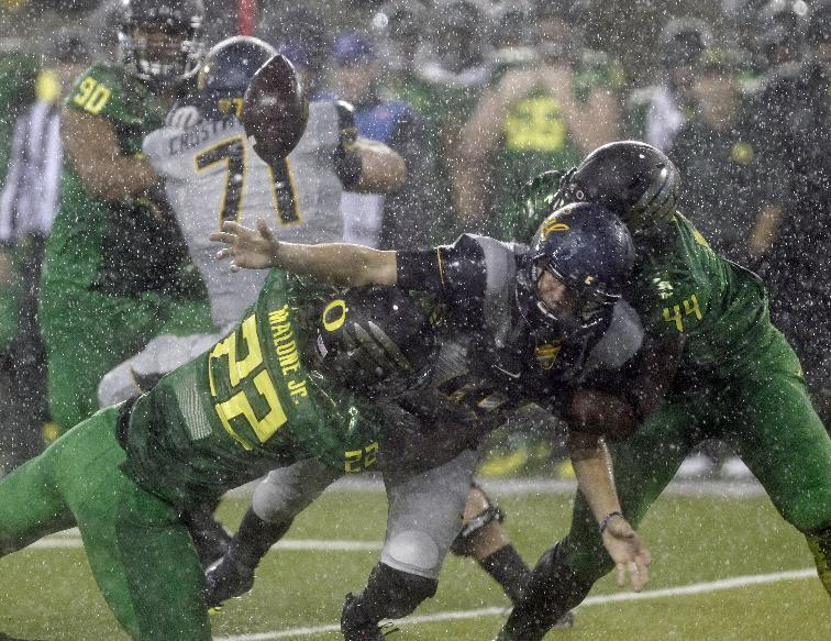 California quarterback Jared Goff, middle, fumbles the ball as he is tackled by Oregon defenders Derrick Malone Jr., left, and DeForest Buckner during the first half of an NCAA college football game in the rain in Eugene, Ore., Saturday, Sept. 28, 2013. (AP Photo/Don Ryan)