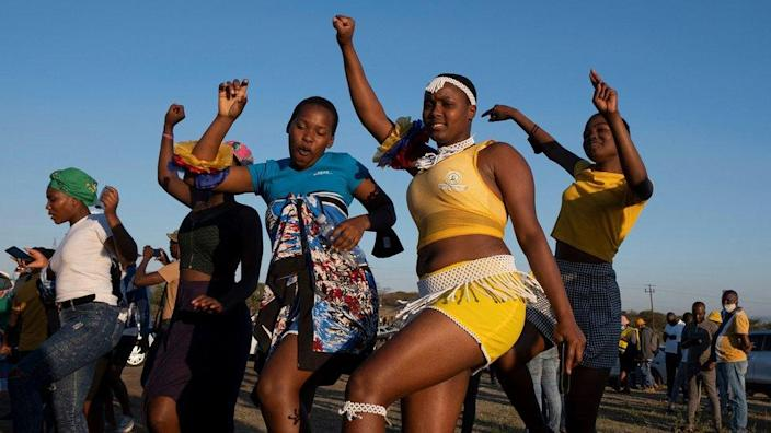 Supporters dance outside the rural home of former South African President Jacob Zuma in Nkandla on July 3, 2021