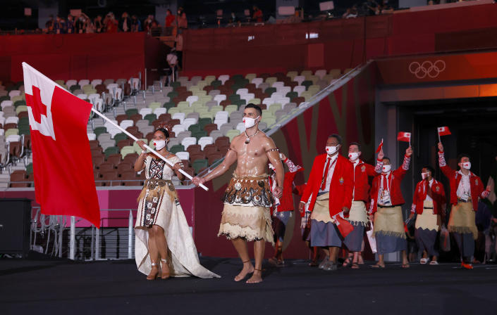 <p>TOKYO, JAPAN - JULY 23: Flag bearers Malia Paseka and Pita Taufatofua of Team Tonga lead their team out during the Opening Ceremony of the Tokyo 2020 Olympic Games at Olympic Stadium on July 23, 2021 in Tokyo, Japan. (Photo by Jamie Squire/Getty Images)</p>