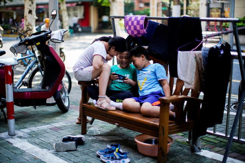 Children look at a phone on a street in Shanghai