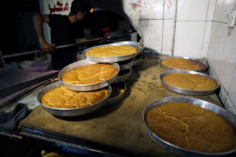 A baker takes dishes of rawani dessert out of a wood-fired oven during the holy month of Ramadan in Sanaa