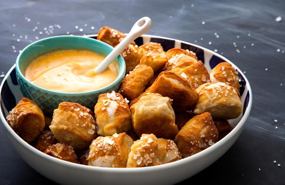 """<p>Pretzels and cheese dip are one of the best stadium foods around. You can be party MVP by bringing these to any gathering. <a href=""""https://www.thedailymeal.com/how-make-soft-pretzels-home?referrer=yahoo&category=beauty_food&include_utm=1&utm_medium=referral&utm_source=yahoo&utm_campaign=feed"""" rel=""""nofollow noopener"""" target=""""_blank"""" data-ylk=""""slk:Making your own pretzels from scratch"""" class=""""link rapid-noclick-resp"""">Making your own pretzels from scratch</a> will guarantee you a spot in the major leagues.</p> <p><a href=""""https://www.thedailymeal.com/best-recipes/pretzel-cheese-dip?referrer=yahoo&category=beauty_food&include_utm=1&utm_medium=referral&utm_source=yahoo&utm_campaign=feed"""" rel=""""nofollow noopener"""" target=""""_blank"""" data-ylk=""""slk:For the Pretzel Bites With Spicy Cheddar Dip recipe, click here."""" class=""""link rapid-noclick-resp"""">For the Pretzel Bites With Spicy Cheddar Dip recipe, click here.</a></p>"""