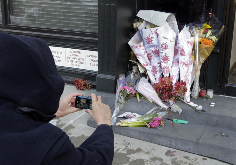 A passerby photographs the flowers placed outside the apartment building of actor Phillip Seymour Hoffman, in New York, Tuesday, Feb. 4, 2014. Autopsy results are expected soon in the death of actor Phillip Seymour Hoffman but police say it may take longer to determine if the heroin found in his apartment contains additives designed intensify the high. (AP Photo/Richard Drew)
