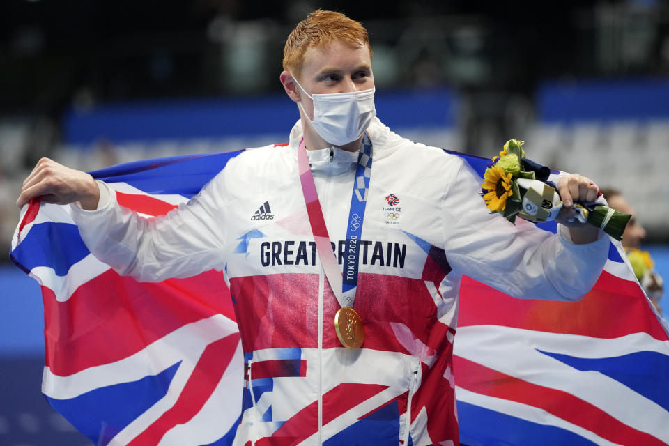 Tom Dean of Britain celebrates after winning the gold medal in the men's 200-meter freestyle at the 2020 Summer Olympics, Tuesday, July 27, 2021, in Tokyo, Japan. (AP Photo/Matthias Schrader)