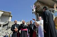 Pope Francis releases a white dove near the ruins of the Syriac Catholic Church of the Immaculate Conception, in the Iraqi city of Mosul on Sunday