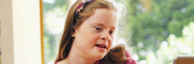 Teenage girl with Down syndrome on her laptop