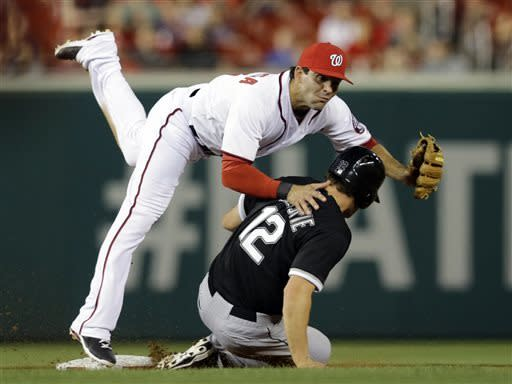 Washington Nationals second baseman Danny Espinosa, top, falls over Chicago White Sox's Conor Gillaspie (12) while turning a double play during the fifth inning of an interleague baseball game at Nationals Park, Wednesday, April 10, 2013, in Washington. (AP Photo/Alex Brandon)