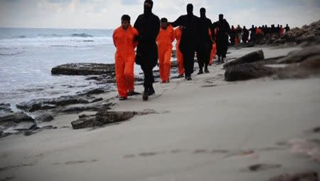 Men in orange jumpsuits purported to be Egyptian Christians held captive by the Islamic State (IS) are marched by armed men along a beach said to be near Tripoli, in this still image from an undated video made available on social media on February 15, 2015. REUTERS/Social media via Reuters TV