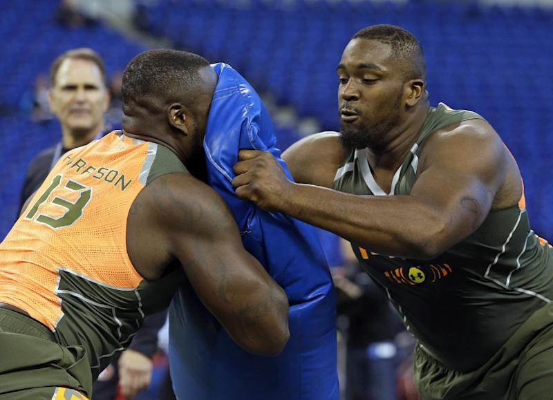 Miami offensive lineman Seantrel Henderson, right, blocks Florida offensive lineman Jonotthan Harrison during a drill at the NFL football scouting combine in Indianapolis, Saturday, Feb. 22, 2014. (AP Photo/Michael Conroy)