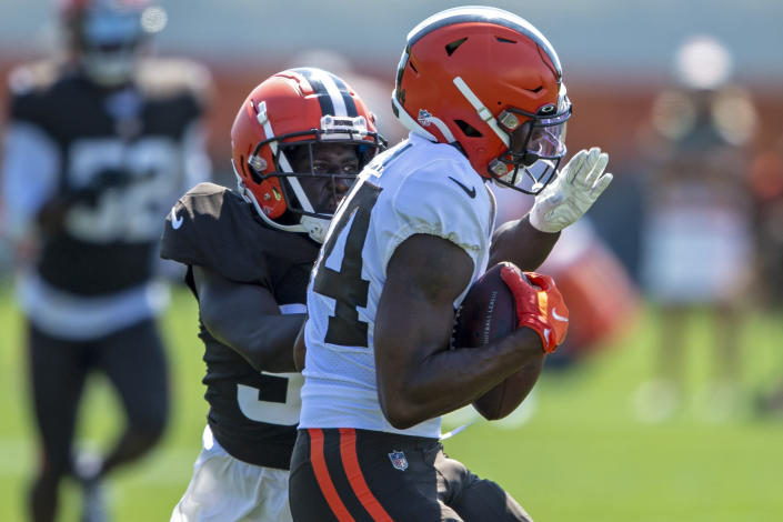 Cleveland Browns defensive back Emmanuel Rugamba, back, breaks up a pass intended for receiver Ja'Marcus Bradley during an NFL football practice in Berea, Ohio, Wednesday, Aug. 4, 2021. (AP Photo/David Dermer)