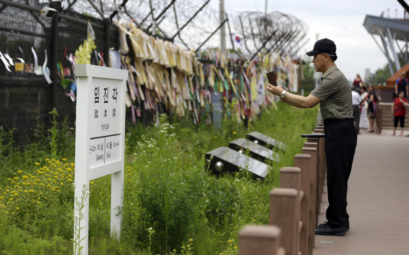 A man takes souvenir photos a directional sign showing the distance to North Korea's Kaesong city and South Korea's capital Seoul at the Imjingak Pavilion near the border village of Panmunjom, which has separated the two Koreas since the Korean War, in Paju, north of Seoul, South Korea, Tuesday, June 11, 2013. The two Koreas will hold their highest-level talks in years Wednesday in an effort to restore scrapped joint economic projects and ease animosity marked by recent threats of nuclear war. That in itself is progress, though there are hints that disputes in their bloody history could thwart efforts to better ties. (AP Photo/Lee Jin-man)