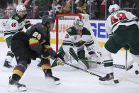 Minnesota Wild goalie Cam Talbot (33) tries to keep the puck away from Vegas Golden Knights center Mattias Janmark (26) during the second period of Game 7 of an NHL hockey Stanley Cup first-round playoff series Friday, May 28, 2021, in Las Vegas. (AP Photo/Joe Buglewicz)