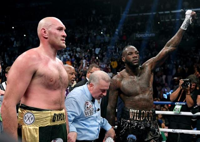 Tyson Fury and Deontay Wilder wait for a decision with referee Jack Reiss before a draw is announced in their WBC heavyweight world title fight in Los Angeles on December 1, 2018 (AFP Photo/Harry How)