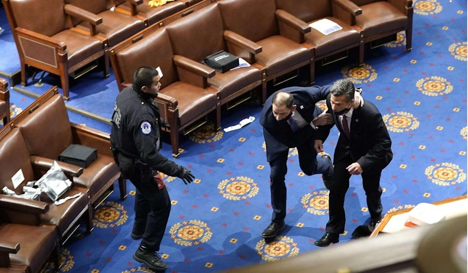 Members of Congress run for cover as protesters try to enter the House chamber. Photo: Getty Images/AFP
