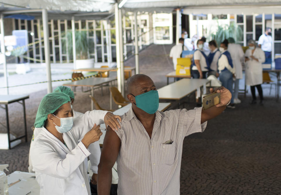 A man takes a selfie as he is injected with a dose of the AstraZeneca COVID-19 vaccine, at a vaccination site set up at the Federal University in Rio de Janeiro, Brazil, Wednesday, June 2, 2021. (AP Photo/Silvia Izquierdo)