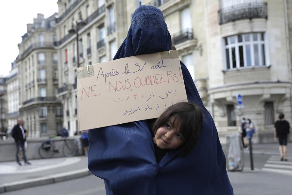 """A woman wearing a burqa and holding a poster reading """"Do not forget us after Aug.31"""" attends a gathering in a show of solidarity with women from Afghanistan, Saturday, Aug. 28, 2021 in Paris. France ended evacuation operations on Friday and its team at the makeshift French Embassy at Kabul's airport pulled up stakes. (AP Photo/Adrienne Surprenant)"""